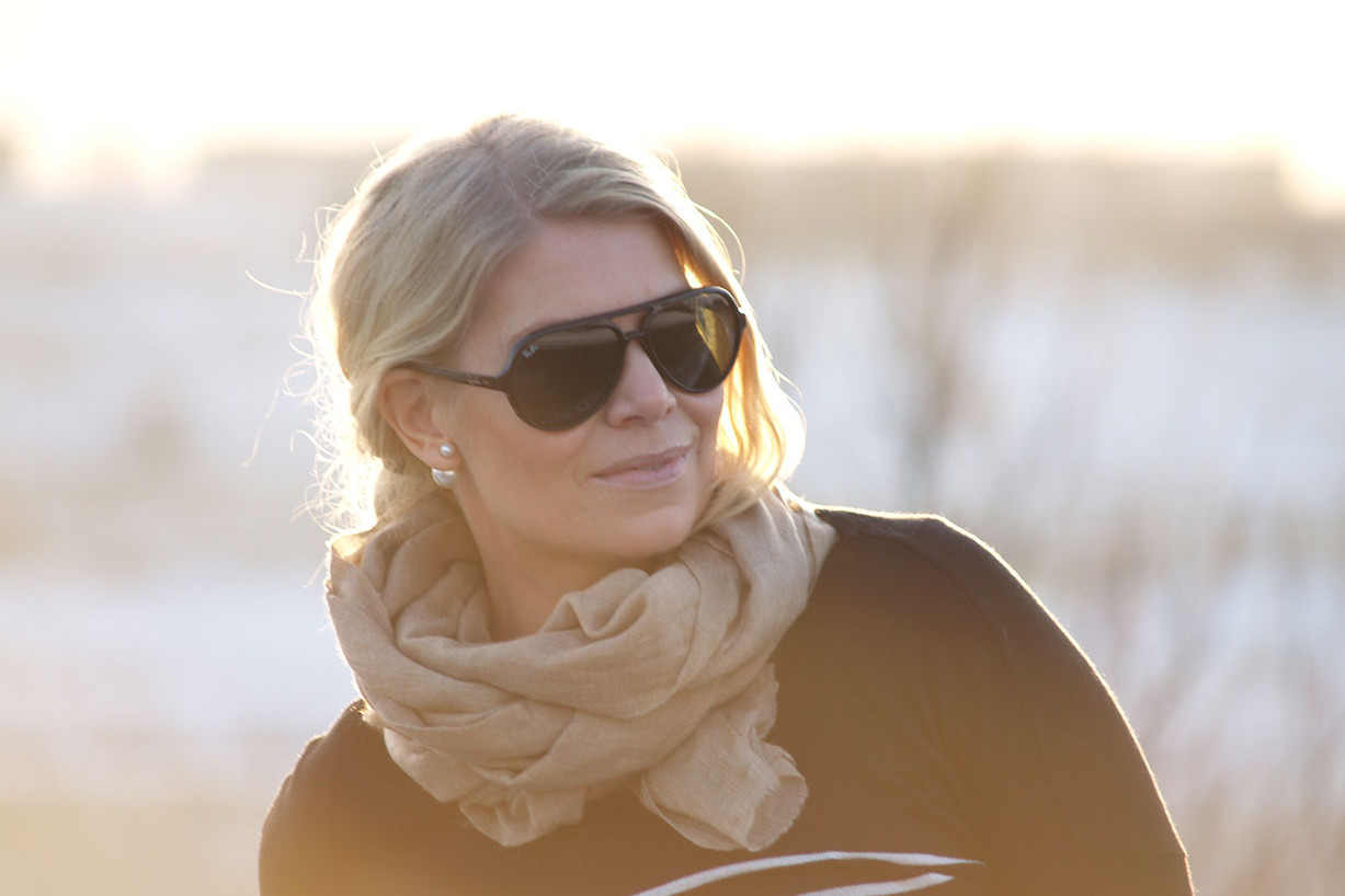 Sunrays in a winter backdrop, blogger Annika Soulcityguide in black Rayban sunglasses and a cashmere scarf
