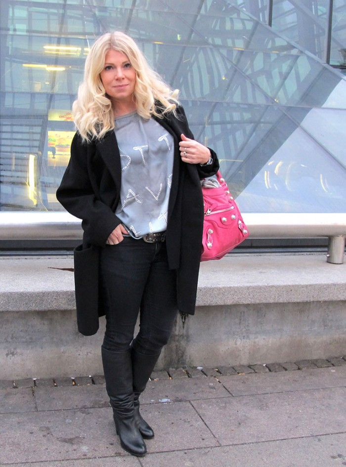 Soulcityguide blogger in front of Malmo Central Station in oversize coat, denim hunter top and pink Balenicaga bag